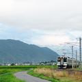 雲に隠れる爺ケ岳鹿島槍五竜岳をバックに松本へ向かう大糸線のローカル電車