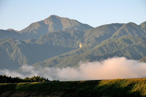 朝日を浴びる甲斐駒ヶ岳と線路にも陽が射す